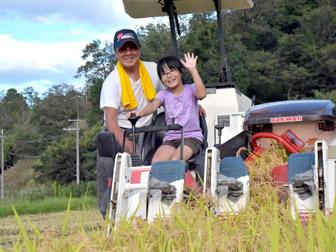 トラクターで稲刈り体験をする子供と農家